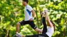 A man and a woman are seen exercising outside in this generic image. (Shutterstock.com)