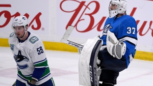Winnipeg Jets goaltender Connor Hellebuyck (37) celebrates his shutout as Vancouver Canucks' Tim Schaller (59) skates off the ice during third period NHL action in Winnipeg on Tuesday Jan. 14, 2020. THE CANADIAN PRESS/Fred Greenslade