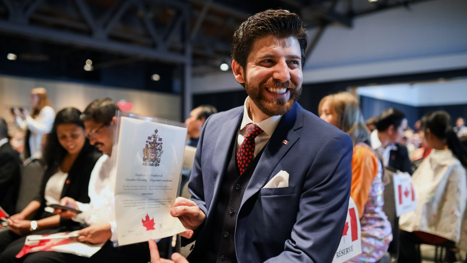 Tareq Hadhad holds his citizenship paper at the Oath of Citizenship ceremony at The Canadian Museum of Immigration at Pier 21 in Halifax on Wednesday, Jan. 15, 2020. (THE CANADIAN PRESS/Riley Smith)
