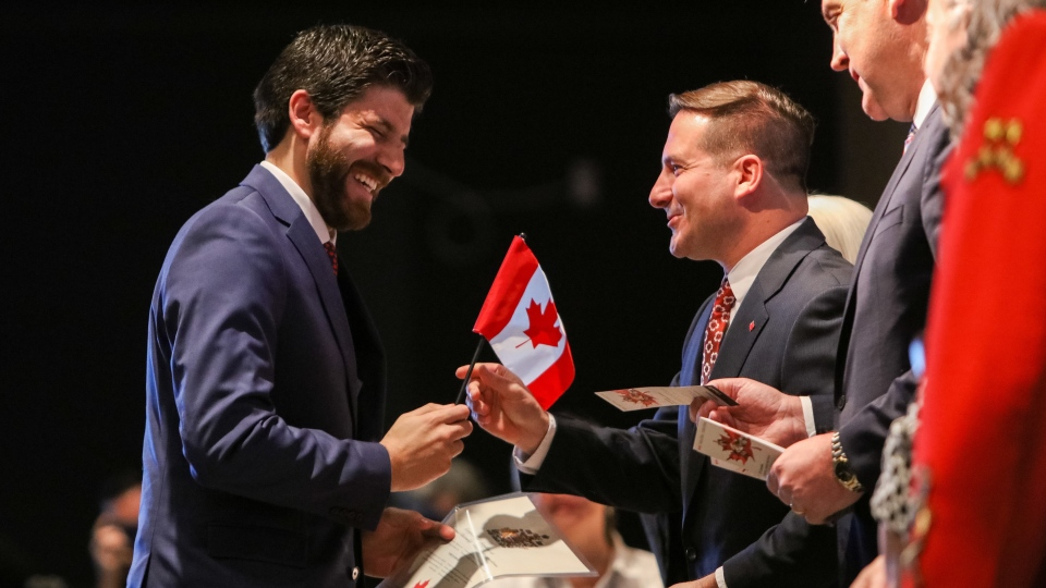 Tareq Hadhad receives a Canadian flag from Minister of Immigration, Refugees and Citizenship Marco Mendicino at the Oath of Citizenship ceremony at The Canadian Museum of Immigration at Pier 21 in Halifax on Wednesday, Jan. 15, 2020. (THE CANADIAN PRESS/Riley Smith)