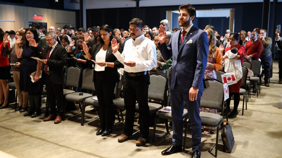 Tareq Hadhad, right, pledges his allegiance at the Oath of Citizenship ceremony at The Canadian Museum of Immigration at Pier 21 in Halifax on Wednesday, Jan. 15, 2020. (THE CANADIAN PRESS/Riley Smith)