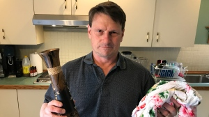 Rejent Guay holds up a vase and some clothing he purchased for his daughter while he was on vacation. (Pat Foran/CTV News Toronto)