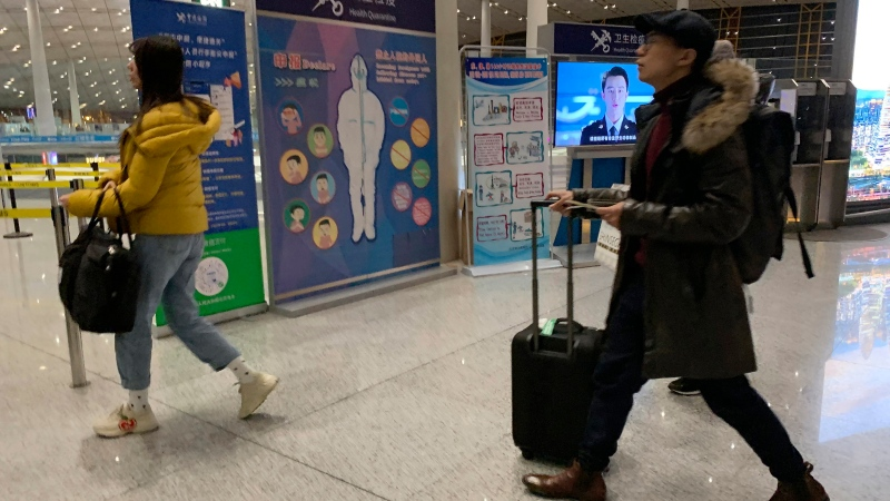 In this Jan. 13, 2020, photo, travelers pass by a health checkpoint before entering immigration at the international airport in Beijing. (AP Photo/Ng Han Guan)