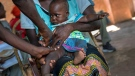 In this photo taken Wednesday, Dec. 11, 2019, health officials vaccine residents of the Malawi village of Tomali, where young children become test subjects for the world's first vaccine against malaria. (AP Photo/Jerome Delay)