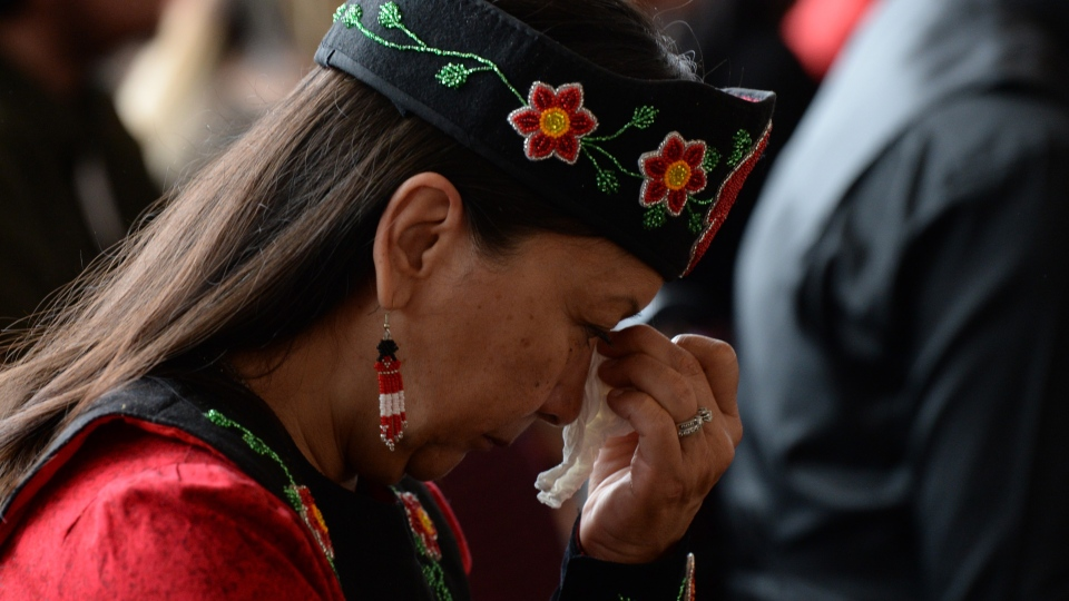 A woman shows her emotions as she listens to speakers during ceremonies marking the release of the Missing and Murdered Indigenous Women report in Gatineau, Monday June 3, 2019. THE CANADIAN PRESS/Adrian Wyld