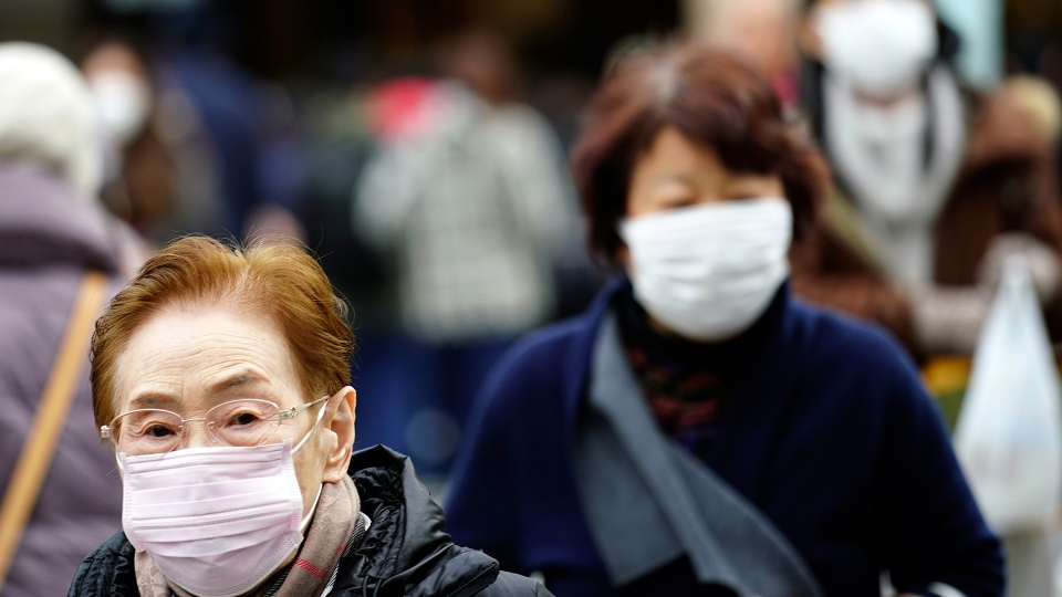 Pedestrians wear protective masks as they walk through a shopping district in Tokyo Thursday, Jan. 16, 2020. (AP Photo/Eugene Hoshiko)
