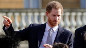 Prince Harry gestures in the gardens of Buckingham Palace in London, Thursday, Jan. 16, 2020. (AP Photo/Kirsty Wigglesworth)