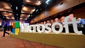In this Nov. 30, 2016, file photo a man walks past a Microsoft sign at the annual Microsoft shareholders meeting in Bellevue, Wash. (AP Photo/Elaine Thompson, File)