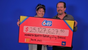 Mona Gibson (L) and Kenneth Beatty (R) pick up their $25 million jackpot cheque from the lottery prize centre in Toronto. Jan. 16, 2020. (OLG)