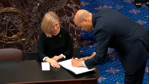 In this image from video, Sen. Cory Booker, D-N.J., signs the oath book after being sworn in for the impeachment trial of U.S. President Donald Trump in the Senate at the U.S. Capitol in Washington, Thursday, Jan. 16, 2020. (Senate Television via AP)
