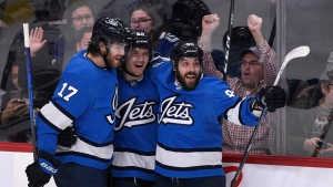Mathieu Perreault (right) celebrates with teammates Jack Roslovic (centre) and Adam Lowry (left) during first period NHL action against the Vancouver Canucks, in Winnipeg on Tuesday Jan. 14, 2020. THE CANADIAN PRESS/Fred Greenslade