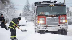 A North Vancouver firefighter shovels a sidewalk in North Vancouver, B.C., Wednesday, January 15, 2020. THE CANADIAN PRESS/Jonathan Hayward