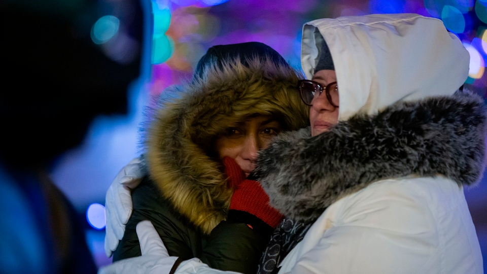People comfort one another during a vigil for those who were among the 176 people who were killed when Ukraine International Airlines Flight PS752 crashed after takeoff near Tehran, Iran, outside the Alberta Legislature Building in Edmonton on Wednesday, Jan. 8, 2020. THE CANADIAN PRESS/Codie McLachlan