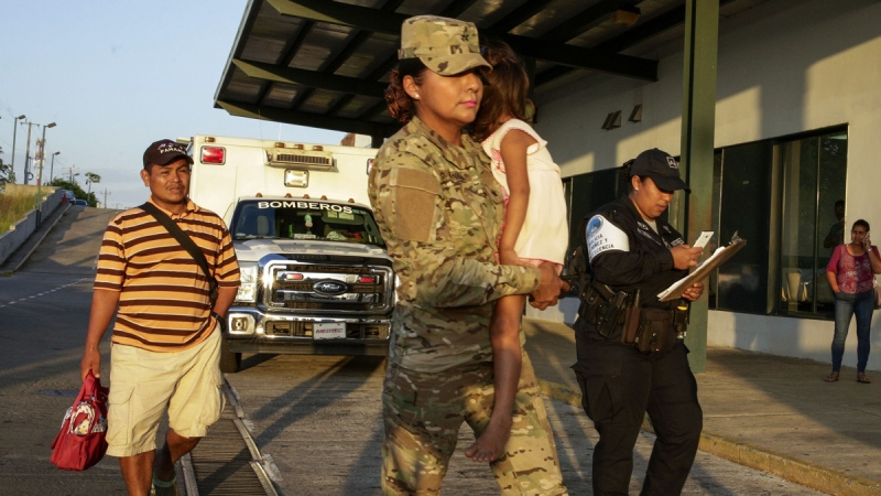 Jose Gonzalez, left, follows his 5-year-old daughter, carried by a police officer, as they leave a hospital in Santiago, Panama, on Jan. 16, 2020. (Arnulfo Franco / AP)