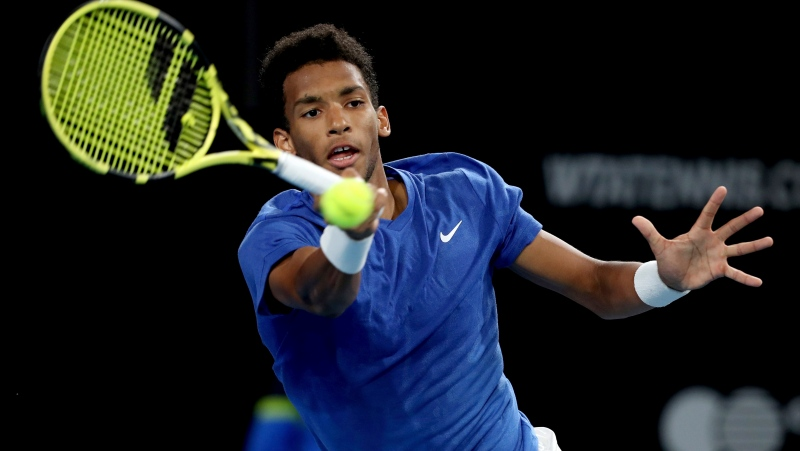 FILE PHOTO: Canada's Felix Auger-Aliassime plays a shot against Russia's Andrey Rublev during their Adelaide International tennis match in Adelaide, Friday, Jan. 17, 2020. (AP Photo/James Elsby