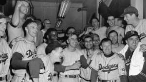 In this September 1951 file photo, Brooklyn Dodgers whoop it up in their dressing room at Shibe Park in Philadelphia after they nosed out the Phillies 9-8 in 14 innings in a baseball game to go into a playoff series with the New York Giants for the National League pennant. Players at left and left foreground are not identified. Others in the front row, left to right, are: Jackie Robinson, Peewee Reese, Roy Campanella, manager Charley Dressen, and Carl Erskine. (AP Photo, File)