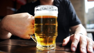A man holding a glass of beer in an outdoor pub. A new CDC study finds an increase in the annual number of drinks consumed during binge-drinking episodes for both men and women between 2011 and 2017. (Dmitry Kostyukov/AFP/Getty Images)