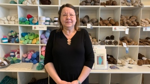 Glenda Hudson stands in front of a yarn display in her store. (Nicole Di Donato/CTV Saskatoon)