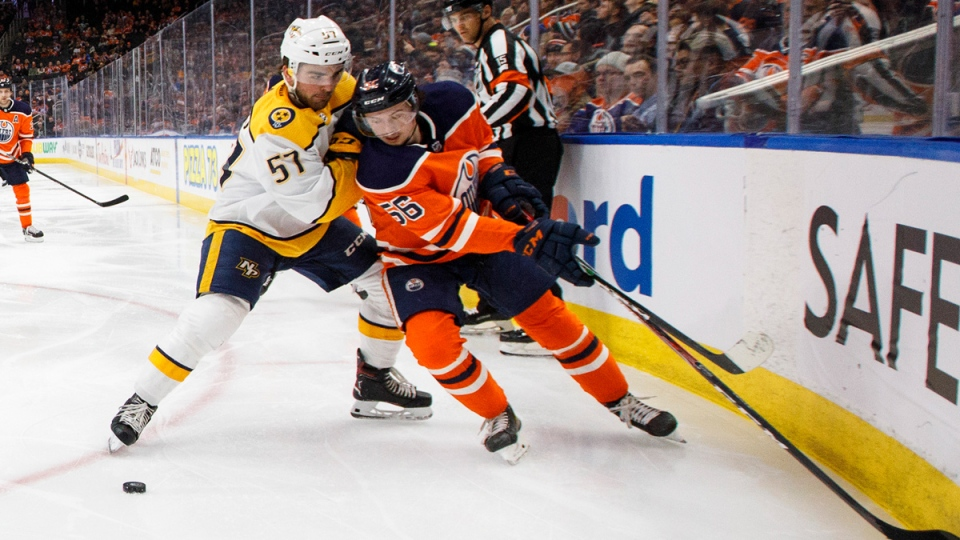 Nashville Predators' Dante Fabbro (57) and Edmonton Oilers' Kailer Yamamoto (56) battle for the puck during second period NHL action in Edmonton, Tuesday, Jan. 14, 2020. THE CANADIAN PRESS/Jason Franson