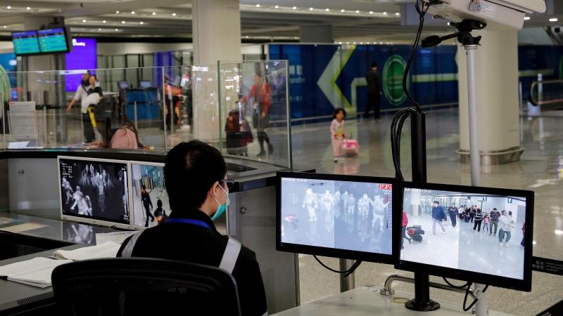 In this Jan. 4, 2020, file photo, a health surveillance officer monitors passengers arriving at the Hong Kong International airport in Hong Kong. (AP Photo/Andy Wong, File)