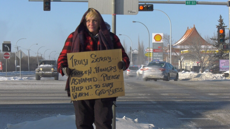 """Leanna holds a sign at a median on 97 Street that reads, """"Frozen. Hungry. Ashamed. Please help us to stay warm. God bless."""""""