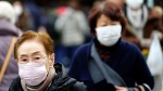 Pedestrians wear protective masks as they walk through a shopping district in Tokyo Thursday, Jan. 16, 2020. (AP Photo/Eugene Hoshiko)