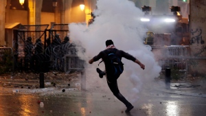 A protester kicks a tear gas canister that was fired towards them by Lebanese riot police during an anti-government protest at a road leading to the parliament building in Beirut, Lebanon, Jan. 18, 2020. (AP Photo/Hassan Ammar)