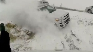 Truck barely misses man as it slides off highway