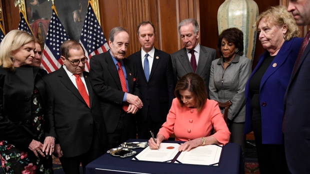 In this Jan. 15, 2020 file photo, House Speaker Nancy Pelosi of Calif., signs the resolution to transmit the two articles of impeachment against U.S. President Donald Trump to the Senate for trial on Capitol Hill in Washington. (AP Photo/Susan Walsh)