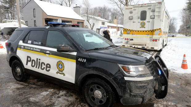 Police vehicles cordon off an area outside a home in Mascouche, Que., Thursday, Jan.16, 2020. Quebec provincial police are investigating the killing of a woman in her 30s inside a home in Mascouche. THE CANADIAN PRESS/Ryan Remiorz