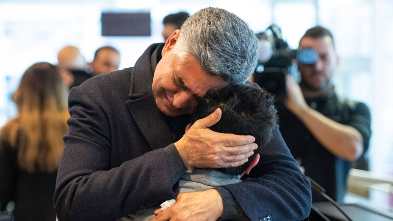 Ryan Pourjam, 13, son of Mansour Pourjam, is embraced by family friend Mahmoud Rastgou, after a ceremony at Carleton University to honour Pourjam, a biology alumnus, and biology PhD student Fareed Arasteh, who died in the crash of Ukraine International Airlines Flight PS752 in Tehran, in Ottawa, on Wednesday, Jan. 15, 2020. THE CANADIAN PRESS/Justin Tang