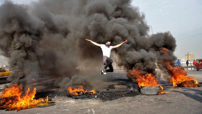 An anti-government protester jumps over burning tires blocking a highway in Baghdad, Iraq, Sunday, Jan. 19, 2020. (AP Photo/Khalid Mohammed)