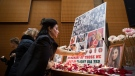 A woman places a candle beneath photographs of some of the people who died in the downing of Ukrainian Airlines Flight 752 in Iran, during a vigil for the victims of the flight, at the Har El synagogue in West Vancouver, on Sunday January 19, 2020. THE CANADIAN PRESS/Darryl Dyck