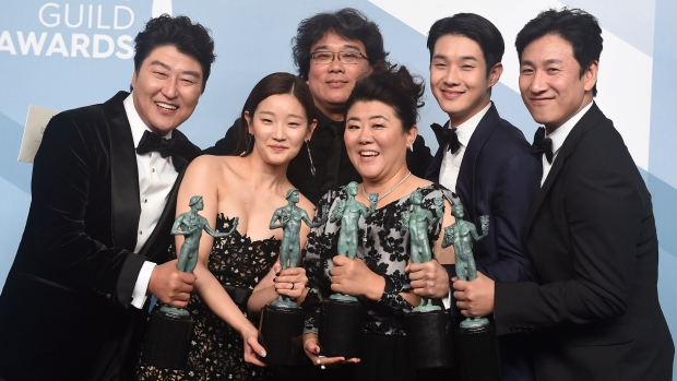 "Kang-Ho Song, from left, Park So-dam, Bong Joon-ho, Jang Hye-jin, Choi Woo-shik, and Lee Sun Gyun pose in the press room with the award for outstanding performance by a cast in a motion picture for ""Parasite"" at the 26th annual Screen Actors Guild Awards at the Shrine Auditorium & Expo Hall on Sunday, Jan. 19, 2020, in Los Angeles. (Photo by Jordan Strauss/Invision/AP)"