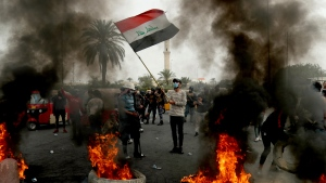 Anti-government protesters set fires and close streets during ongoing protests in downtown Baghdad, Iraq, Sunday, Jan. 19, 2020. (AP Photo/Hadi Mizban)