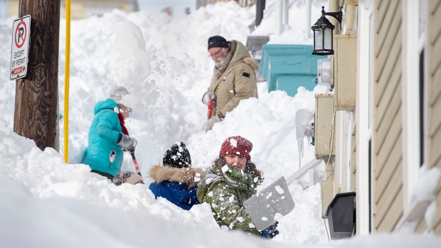 Residents shovel their sidewalk in St. John's on Sunday, Jan. 19, 2020. The state of emergency ordered by the City of St. John's continues, leaving businesses closed and vehicles off the roads in the aftermath of the major winter storm that hit the Newfoundland and Labrador capital. THE CANADIAN PRESS/Andrew Vaughan