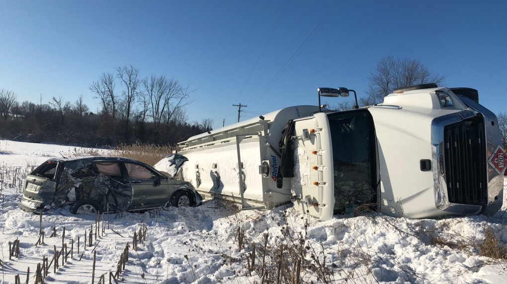 A transport truck on its side next to a car