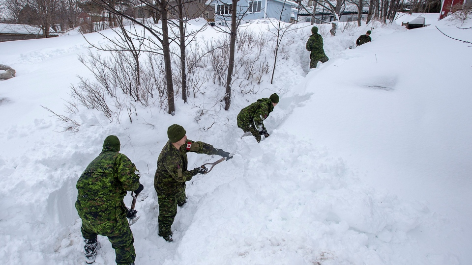 Soldiers from the 4th Artillery Regiment based at CFB Gagetown clear snow at a residence in St. John's on Monday, January 20, 2020.  (THE CANADIAN PRESS/Andrew Vaughan)