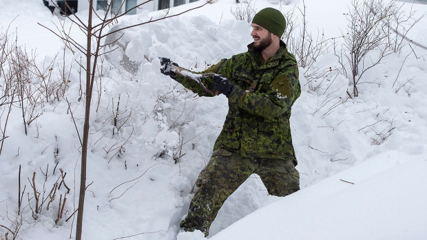 A soldier from the 4th Artillery Regiment based at CFB Gagetown clears snow at a residence in St. John's on Monday, January 20, 2020. THE CANADIAN PRESS/Andrew Vaughan