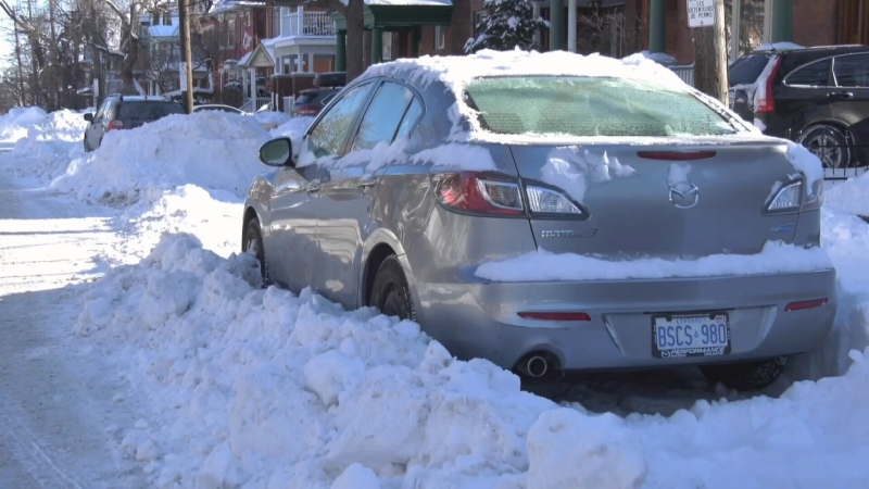 City crews plow streets around parked cars after record setting snowfall on the weekend.