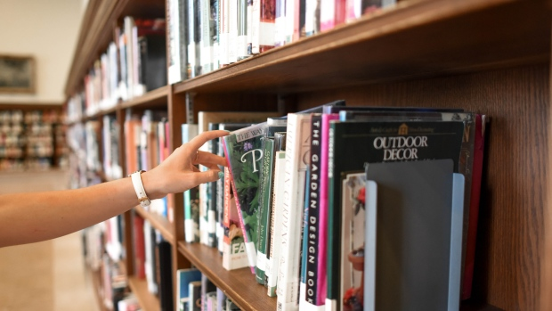 Person holding book from shelf (Pexels)