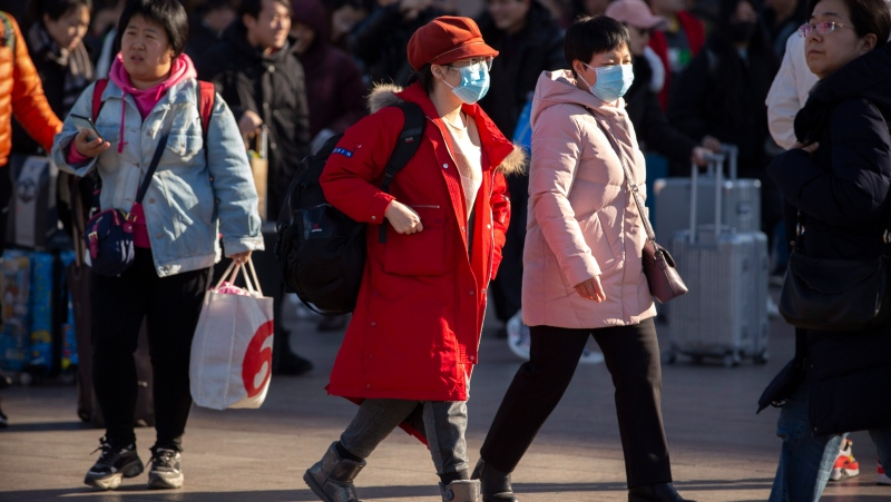 Travellers wear face masks as they walk outside of the Beijing Railway Station in Beijing, Monday, Jan. 20, 2020. (AP Photo/Mark Schiefelbein)