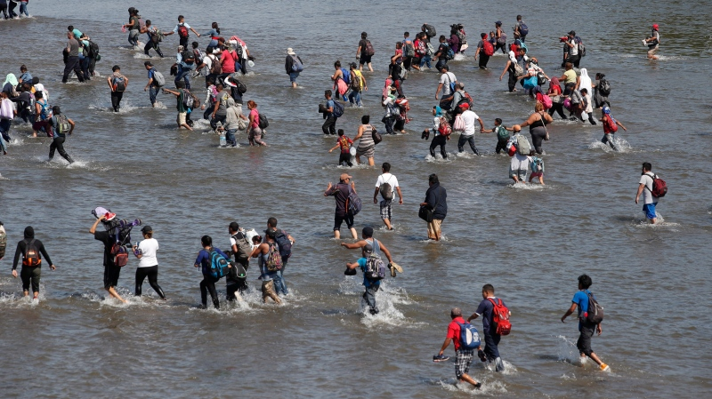 Central American migrants cross the Suchiate River by foot from Tecun Uman, Guatemala, to Mexico, Monday, Jan. 20, 2020. (AP Photo/Moises Castillo)