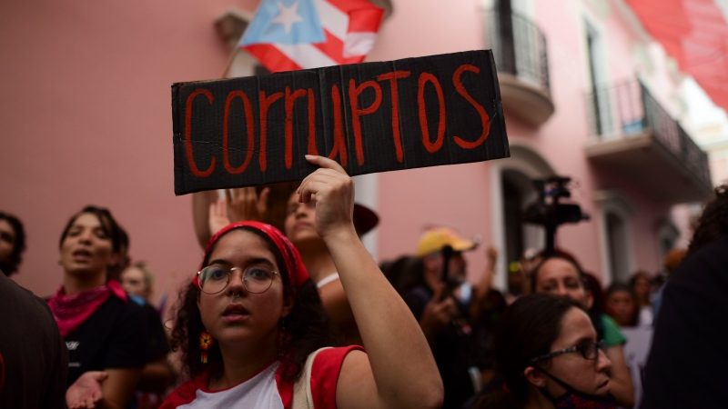 "A young woman holds a sign that reads in Spanish ""Corrupt"" while protesting outside the executive mansion known as La Fortaleza, in Old San Juan, demanding the resignation of Governor Wanda Vazquez after the discovery of an old warehouse filled with unused emergency supplies in San Juan, Puerto Rico, Monday, Jan. 20, 2020. (AP Photo/Carlos Giusti)"