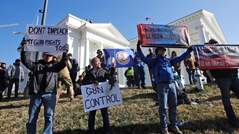 A pro gun demonstrators hold a flag and signs in front of the Virginia State Capitol Monday, Jan. 20, 2020, in Richmond, Va. (AP Photo/Steve Helber)