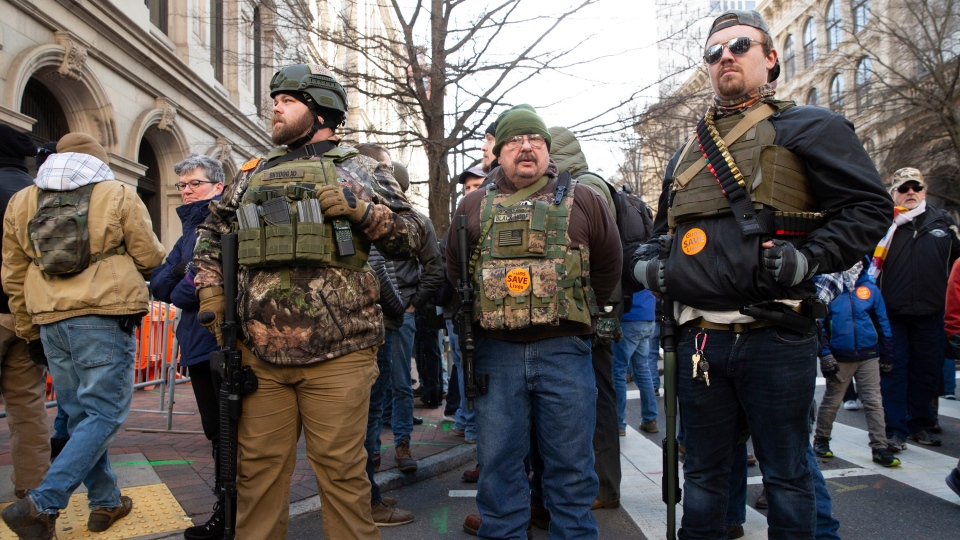 Gun-rights advocates, from Ohio, stand in downtown Richmond, Va., during a gun-rights rally at the Virginia State Capitol, Monday, Jan. 20, 2020. (Mike Morones/The Free Lance-Star via AP)