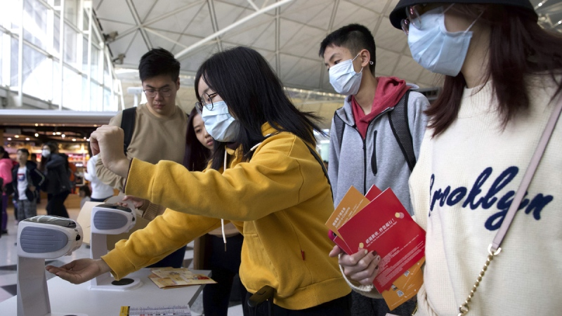 Travellers wearing face masks at Hong Kong International Airport on Jan. 21, 2020. (Ng Han Guan / AP)