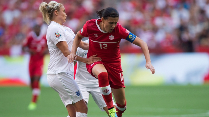 Canada's Christine Sinclair, right, leaps past a challenge from England's Steph Houghton during second half FIFA Women's World Cup quarter-final soccer action in Vancouver, B.C., on Saturday June 27, 2015. THE CANADIAN PRESS/Darryl Dyck