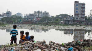 In this June 4, 2018, file photo, Bangladeshi children sit on garbage piled up by the river Buriganga in Hazaribagh area in Dhaka, Bangladesh. (AP Photo/A.M. Ahad, File)