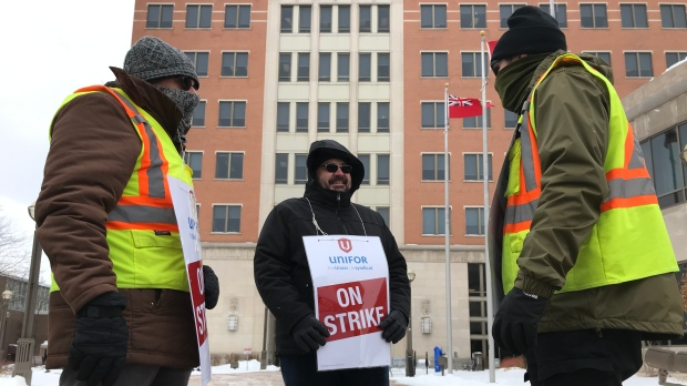 Three Grand River Transit employees seen striking in front of the Region of Waterloo building. (Dan Lauckner / CTV Kitchener)